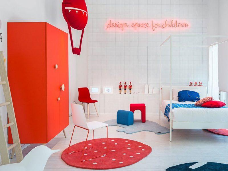 Tenere in ordine cameretta con una cameretta Nidi Design rossa e bianca, con scrivania e lettino bianchi e tappetto e armadio rosso