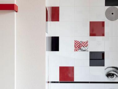Rivestimento bagno moderno, piastrelle Fornasettiana di Fornasetti per Ceramica Bardelli in un bagno vintage, bianco nero e rosso realizzato da Architempore