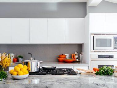 Cucina in marmo con accessori, pentole le creuset e frutta per accessori plastic free